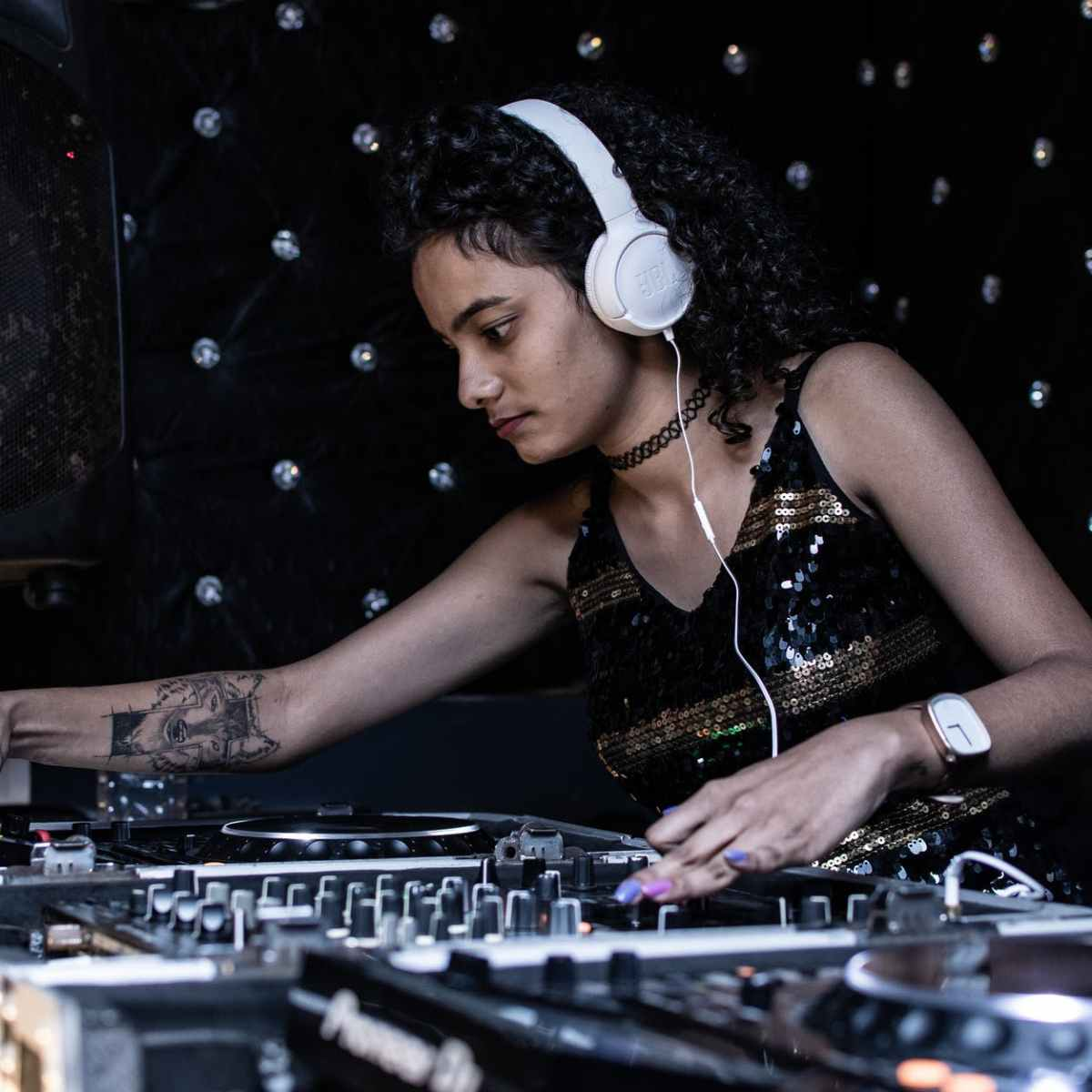 focused ethnic female dj playing music at nightclub