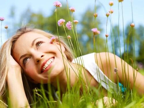 Mulher em jardim pensando em seus sonhos