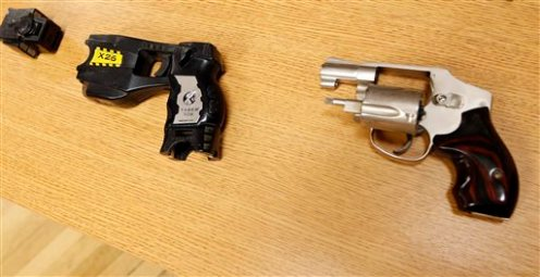 In this Friday, April 10, 2015, photo, a Taser and handgun, similar to the weapons in possession of Tulsa County reserve deputy Robert Bates during a pursuit of Eric Harris, are displayed in Tulsa, Okla. Police say Bates thought he was holding a Taser, not his handgun, when he fatally shot Harris during an arrest that was caught on video in Tulsa. (Cory Young/Tulsa World via AP)