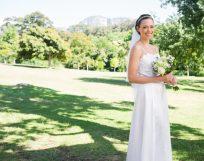 Portrait of happy bride holding flower bouquet in garden