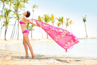 Beach woman pretty, happy and blissful enjoying travel vacation. Beautiful young Asian female bikini model stretching arms holding pink scarf blowing in wind. Big Island, Hawaii, USA.