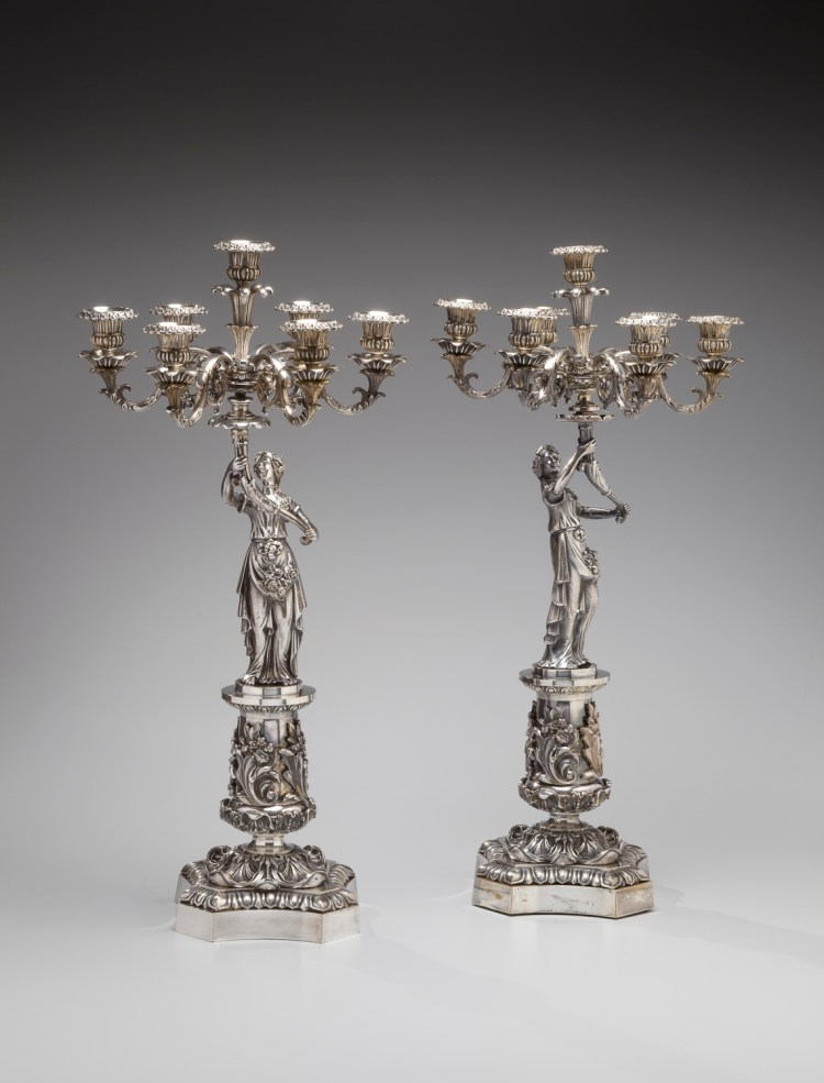 Pair of Figural Candelabrum: Each with seven candle holders extending from scrolled arms on a shaft issuing from a cornucopia held aloft by maidens standing on cylindrical pedestals with applied acanthus-leaf decoration, on stepped abacus-shaped bases. Height: 24¼ inches