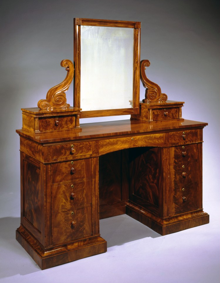 "Bureau with Attached Mirror: The coved rectangular dressing mirror frame suspended from flanking carved scrolled brackets on two short drawers with flanking colonettes set back on a knee-hole or pedestal-end case with four drawers in each pedestal-end with an arched central drawer, resting on a molded base. H 66¾"", W 57½"", D 21½"""