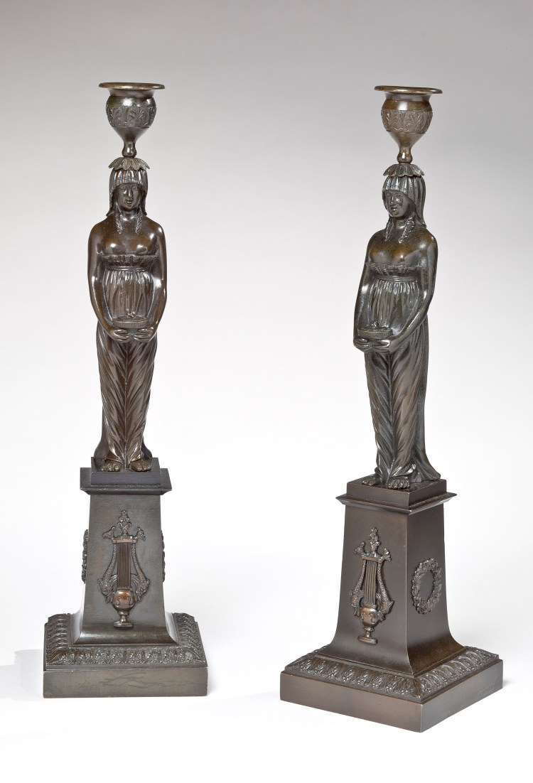Pair of patinated bronze candle sticks formed of Classical maidens in diaphanous gowns supporting candle cups on their heads and holding oil lamps at their waists, standing on rectangular plinth bases with applied decoration of lyres and wreaths.    H: 14½""