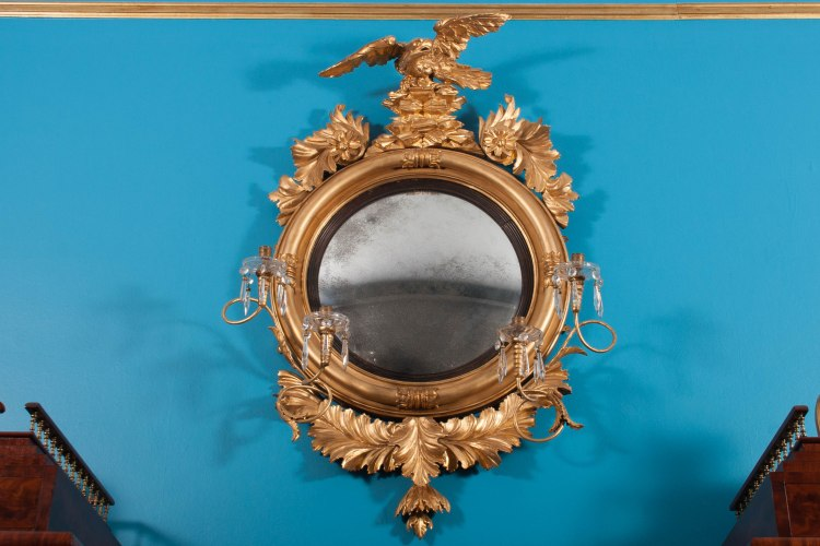 """Convex Girandole Mirror : Having a circular frame with tubular framing device and reeded and ebonized liner around a convex mirror plate surmounted by a rockery and spread-winged eagle, flaked by foliate decoration and four candle arms and having an elaborate carved foliate pendant.  Measure:  H: 45"""" D: 26"""" frame. / candle arms: 32""""."""