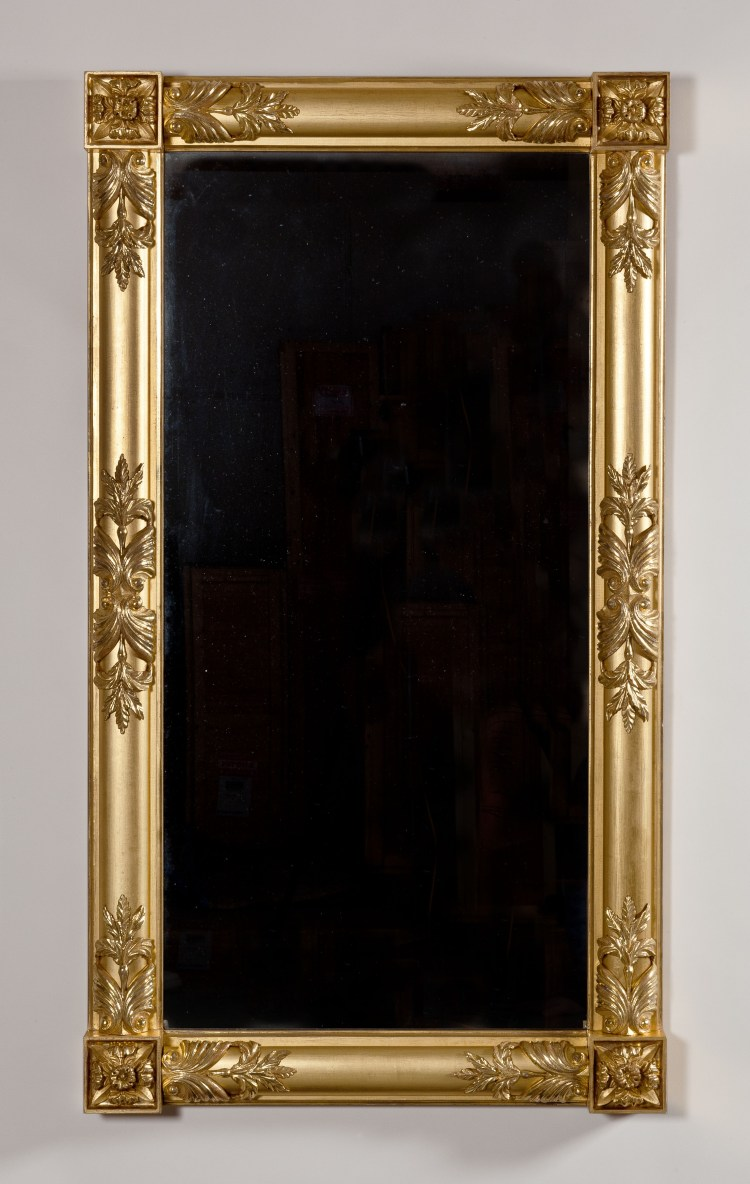"Classical Carved Gilt-wood Pier/ Over-Mantle Mirror:  A rectangular frame with engaged suppressed columns all around terminating in squared rosettes at the corners.  Carved and burnish-gilded leaves are applied to the columns and emanate from the corner rosettes.  Carved foliate elements are also positioned mid-span between top and bottom of the long columns.  Typical of period gilding, there is contrast between the matte gilding of the frame and the burnished gilding of the decorative carving. 28⅝"" x 51"""