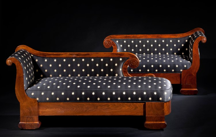"Pair of Rosewood Grecian Couches by Phyfe: Each with undulating veneered crest rail terminating in two scrolls with concentric circle bosses above an upholstered back and seat with a scrolled arm at one end with a matching boss in the volute. The highly figured seat rail raised on flat rectangular legs terminating in suppressed demilune feet with recessed casters.  H: 34"" L: 74""  D: 24"" each"