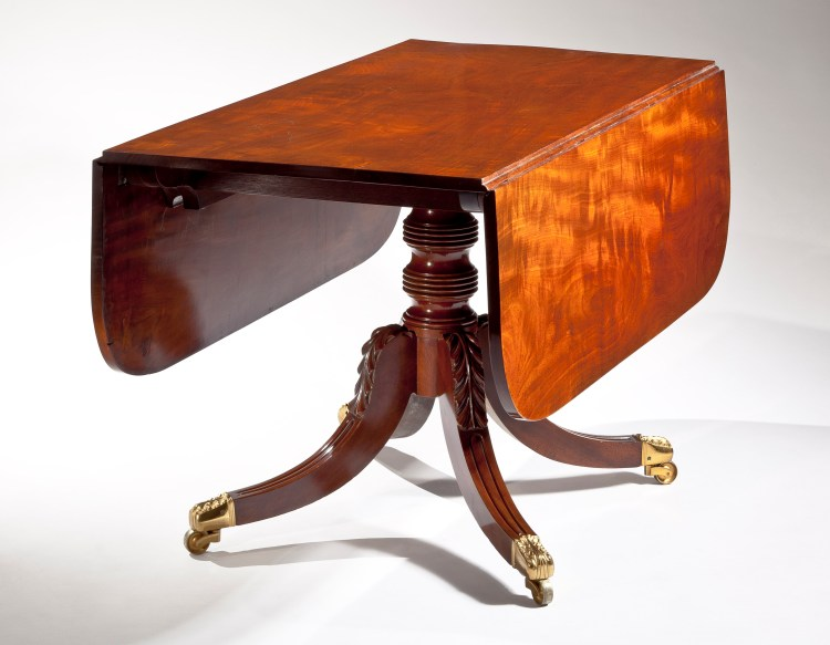 """Dining Table by Duncan Phyfe: Leaves down; The figured solid mahogany top with D-shaped drop leaves on a single ring-turned pedestal raised on saber legs with distinctive acanthus carving at the knees, terminating in elaborate brass toe caps with casters. H: 28¼""""  D: 48""""  W: 24""""  W: open, 54"""""""