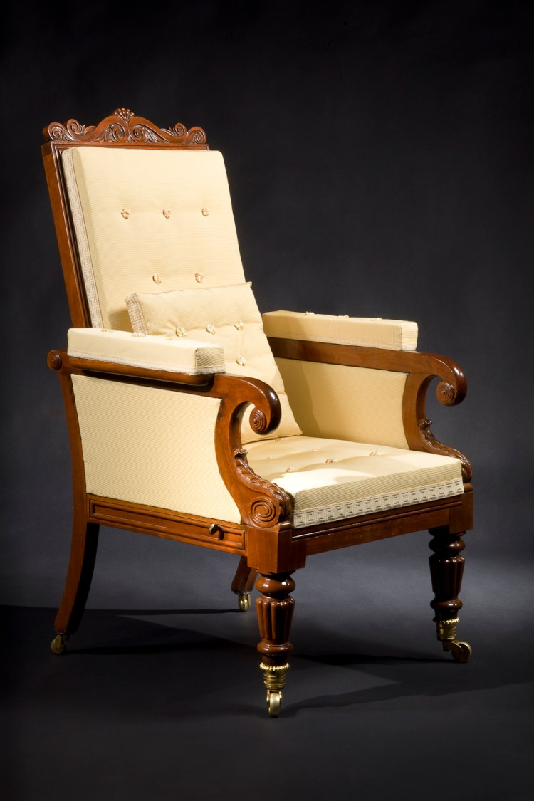 """Classical Mechanical Easy Chair: The lotus-carved arched crest rail above a beaded frame holding an upholstered back, hinged at the base, allowing the back to recline as the upholstered seat slides forward. The padded arm rests terminating in scrolls decorated with tiered, concentric bosses and supported by water-leaf carved scrolls, above turned and reeded front legs terminating in important gilt bronze cup casters. The rear saber legs having brass caster wheels.  H: 46½"""" W: 27¼""""  D: 29"""""""