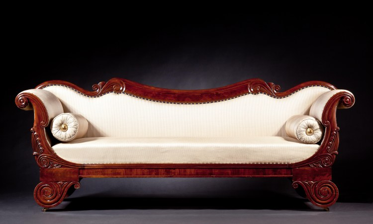 "Restauration Carved Mahogany Grecian Sofa: With a highly figured, shaped crest with carved volutes above an upholstered back and anthemion-carved broken scroll arms, the upholstered seat above a paneled seat rail raised on lotus-carved volute feet, on castors. Height: 35"",  Length: 87½"",  Depth: 24¼"""