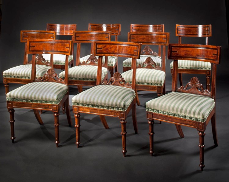 Set of Ten Dining Chairs by Richard Parkin:  The assembled set with Klismos-type curved crest rail with incised border and flame walnut veneer supported by paneled styles, a highly distinctive stay rail of a stylized anthemion issuing scrolls sits above an upholstered seat with paneled seat rail and paneled dies above the turned, tapering front legs with Gothic-type decoration.