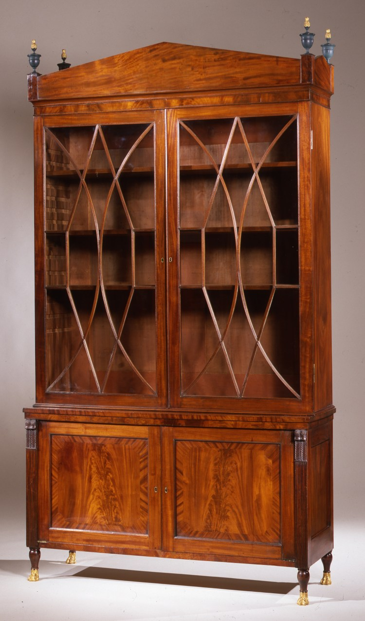 "Federal Bookcase with brass paw feet: In three parts; the arched pediment above a bookcase with glazed doors opening to three adjustable shelves above a case with a pair of cross banded paneled cabinet doors flanked by carved feather and thistle elements forming the capitals of reeded pilasters, raised on short turned vase-form Sheraton legs terminating in brass paw feet. H: 98""  W: 54¼""  D: 18"""