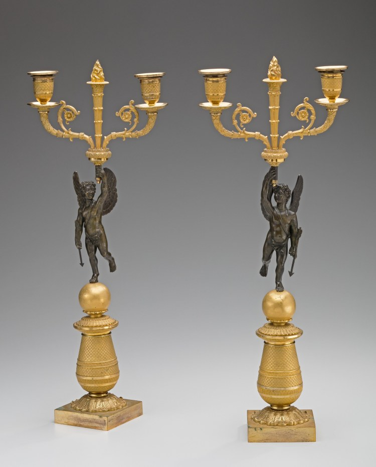 """Pair of Restauration Gilt-Bronze Candelabra with patinated cherubs holding a flaming torch centering a pair of candle arms.  The cherubs stands on a ball above a conical standard above a square plinth.  H: 19½"""""""