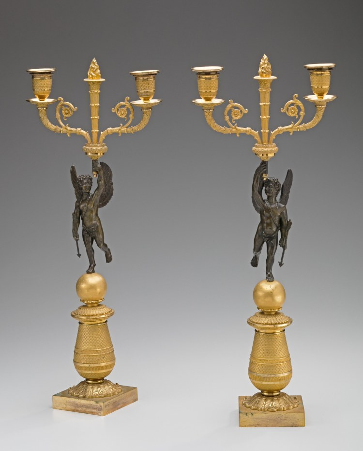 Pair of Restauration Gilt-Bronze Candelabra with patinated cherubs holding a flaming torch centering a pair of candle arms.  The cherubs stands on a ball above a conical standard above a square plinth.  H: 19½""
