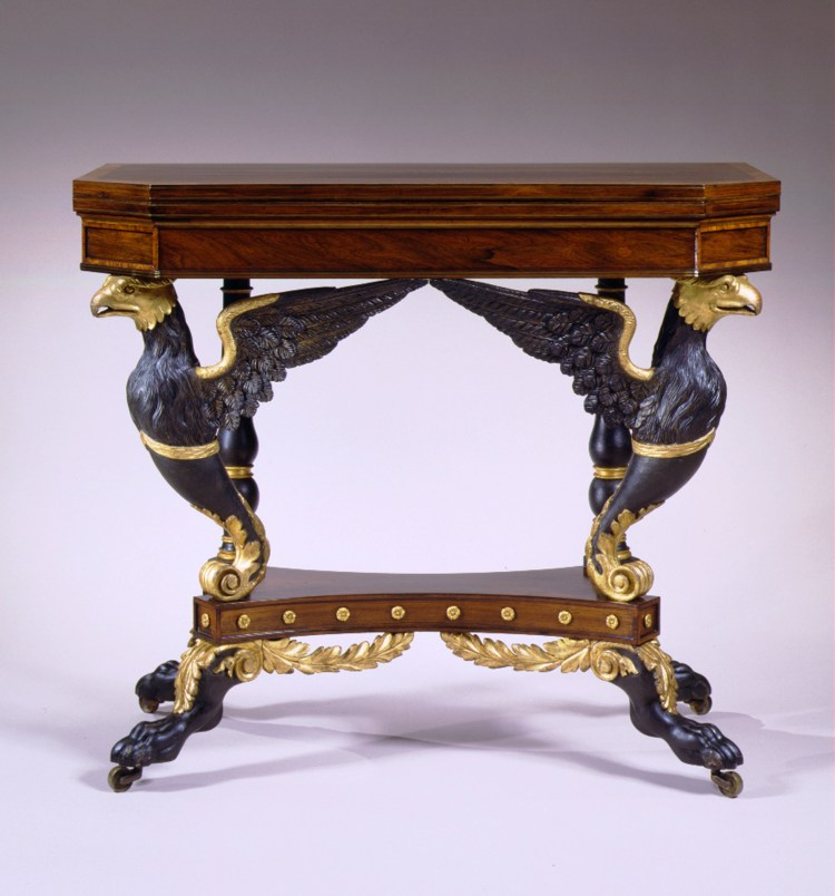 "Eagle-Carved Parcel-Gilt Card Table by Duncan Phyfe: Front view; The hinged swiveling oblong top with canted corners, brass stringing and burl wood cross banding, opening to a well lined with patterned paper, the case with a conforming apron, the canted corners paneled with burl wood, the top edge and apron bottom decorated with brass stringing, above a pair of outward-facing gilt and vert-antique painted, carved eagles, supported in the rear by gilded and painted baluster and ring turned posts all raised on an abacus shaped base its sides punctuated by gilded rosettes and at the corners, four gilt and vert-antique decorated acanthus carved hocked animal paw legs, with gilded acanthus carved brackets in front, extending beneath the base to almost touch each other, the animal paw feet raised on brass casters.  H: 30½""  W: 36""   D: 18½"""