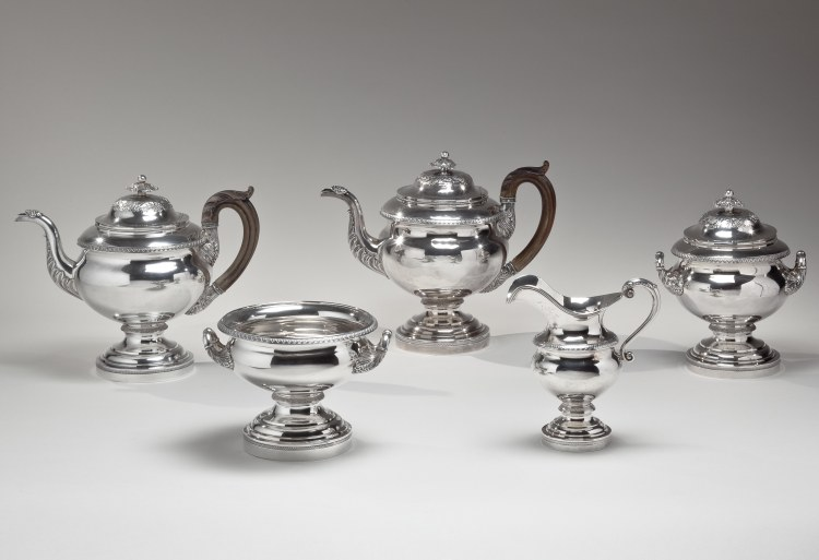 "Coin Silver Tea Service by Fletcher and Gardiner, Comprising: 2 Tea Pots h: 9.75"", Lidded Sugar Bowl h: 8.25"", Cream Pitcher h: 7"" & Waste, Bowl h: 5.5"", Each piece on a footed stand and with repoussé, chased, die-rolled and cast decoration, the tea pots with original carved wood handles."