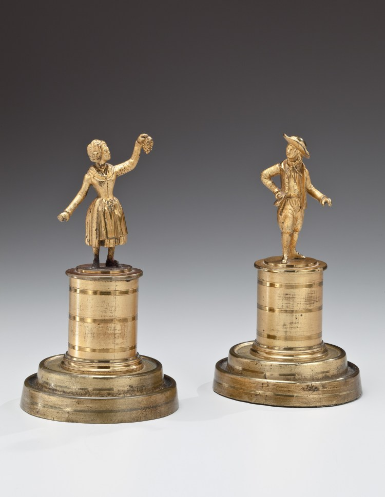Pair of Brass early 19th century figures, a man in a hat and awoman holding up a bunch of grapes, on cylindrical plinths and stepped bases.  Retaining original lacquered two-tone matte and burnished finish.   H: 6""