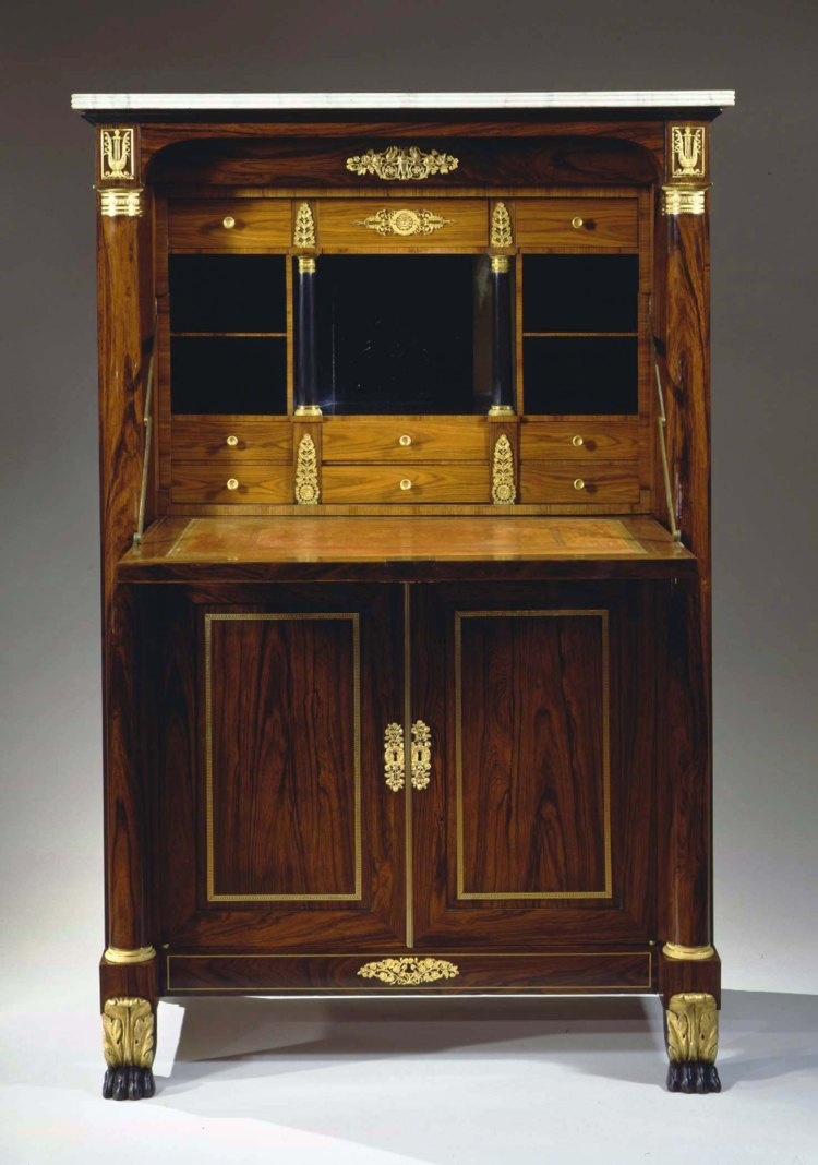 SECRÉTAIRE À ABATTANT by Duncan Phyfe, New York, c. 1820.  Fall front desk open revealing a symmetrical interior with three short drawers across the top above a stacked pair of cubby holes flanking a mirrored compartment above three stacked pairs of drawers, the drawers in King wood with gilt-bronze appliques and pulls.