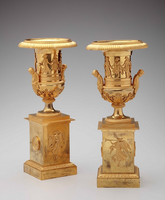 Pair of French Gilt-Bronze Campana Urns by marked Pignot: Each having applied dancing figures around the urns with handles in the form of cherubs, each on a rectangular plinth base with applied decoration of the angel Gabriel.