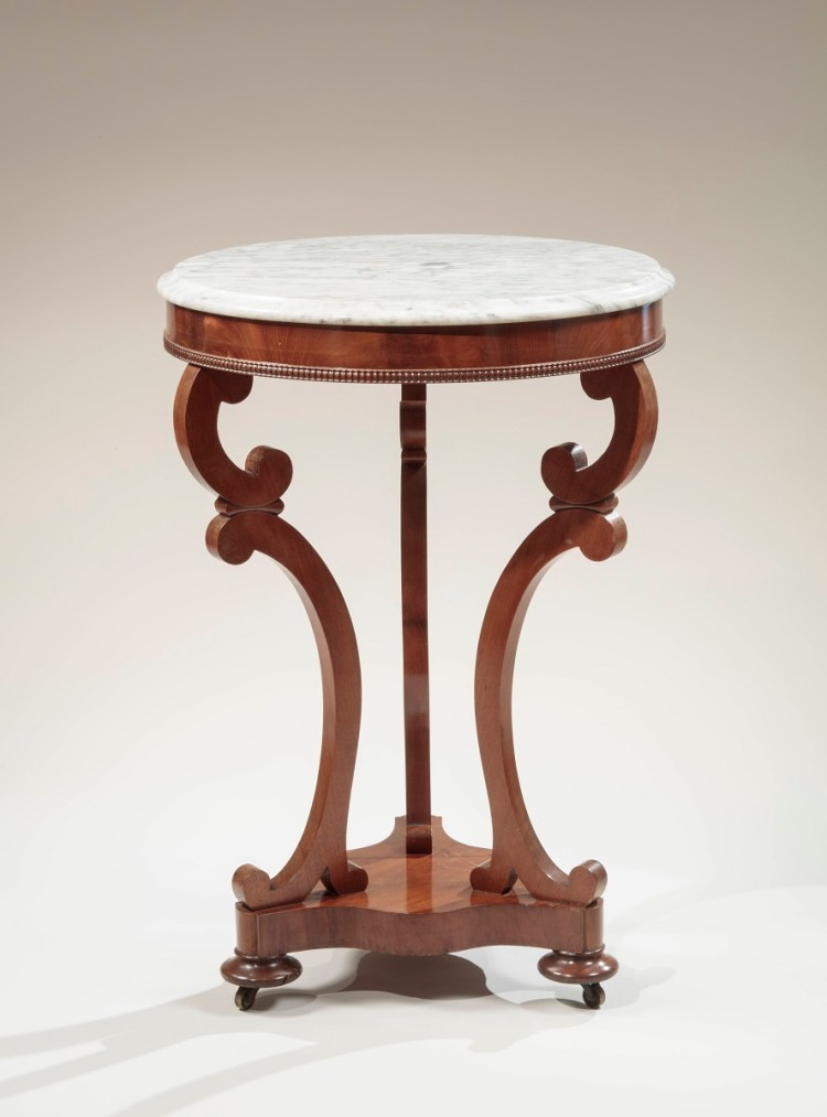 "Mahogany GUERIDON (tripod candle stand), by Brown & Hand:  The circular Carrara marble top with molded edge above a conforming skirt with applied spooling at the bottom edge, above three  ""C"" and ""S"" shaped scrolling legs raised on a serpentine-shaped plinth on three turned pad feet, raised on brass castors."