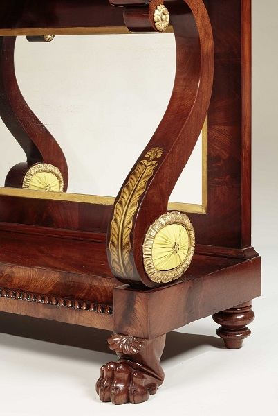PAIR OF RESTAURATION PIER TABLES: Detail of gilt-stencil leaf on the front of the scrolled support and the elliptical boss with gathered upholstery.