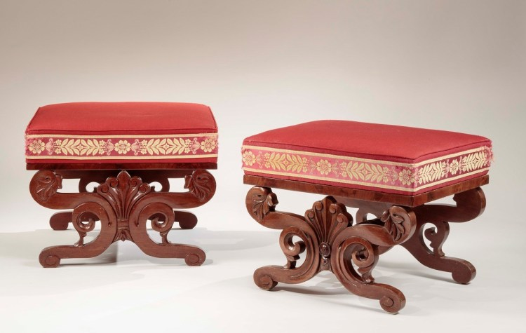 """Two mahogany stools each with an upholstered slip seat in red fabric banded with red and gold passementrie tape, above a veneered plinth supported on two sides by a carved anthemion held in carved S scrolls which form the legs, connected by a bold turned stretcher. H: 18½"""" W: 22""""  D: 18""""  /  H: 17""""  W: 23""""  D: 23'"""
