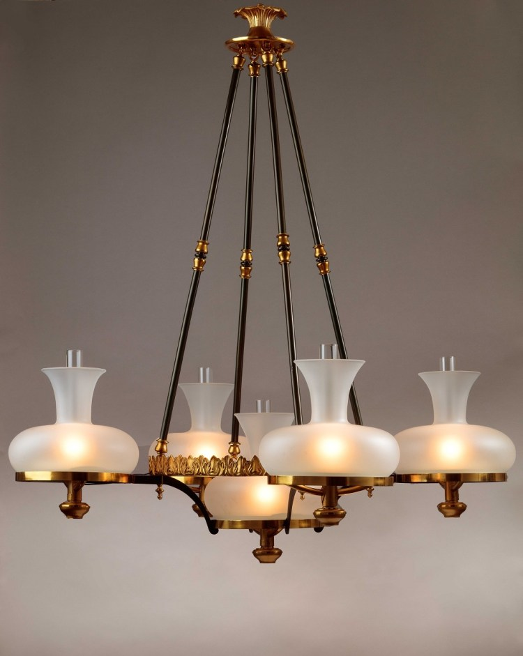 Simunbra Chandelier having a foliate canopy above four pendant patinated rods supporting a circular cast foliate ring with four satellite extension rings holding sinumbra fonts with a fifth font suspended directly below the primary ring. Each burner tube bearing a label: MANUFACTURED BY/ H.N. HOOPER & CO./ BOSTON.