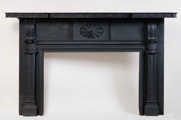 Carved Federal Mantelpiece with original black paint, having a shaped shelf above a frieze centering a fan-carved rosette above the fire box, flanked by jams with corbels above reeded engaged columns with foliate capitals and stepped bases.