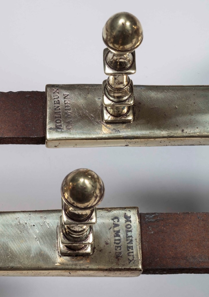 "Pair of Brass Andirons with brass shaft with ""lemon"" finials on a square plinth above cabriole legs with spurs at the knees terminating in slipper feet, conforming-shape brass log stop and iron billet bar. Each bearing the foundry mark MOLINEUX/CAMDEN. H: 19.5 inches  D: 20.5 inches"