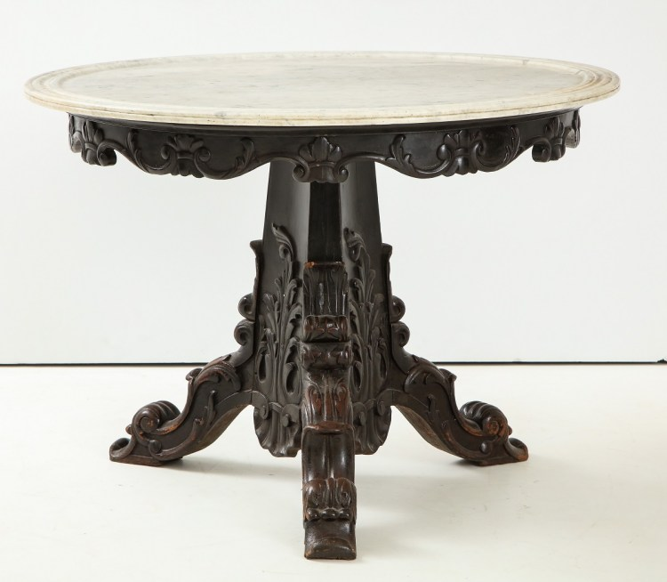 Anglo-Indian Center Table with circular white marble top with molded edge above a carved, ebonized, conforming apron on a carved, pylon-shaped pedestal raised on three carved, scrolled legs.