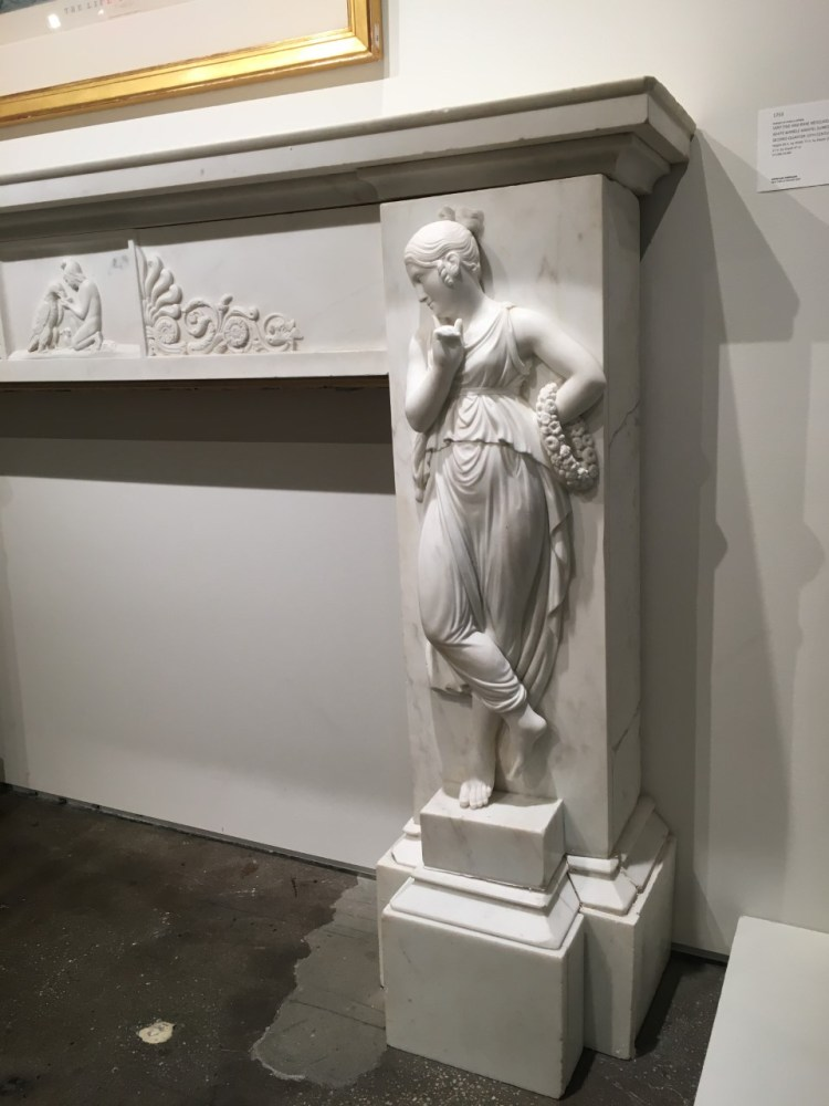 Carved marble dancing figures after Antonio Canova flank the fire box. This figure is on the proper left of the firebox.