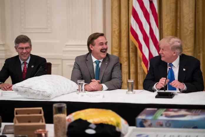 """Mike Lindell laughs with President Donald Trump during a """"Made in America,"""" roundtable event in the East Room at the White House."""