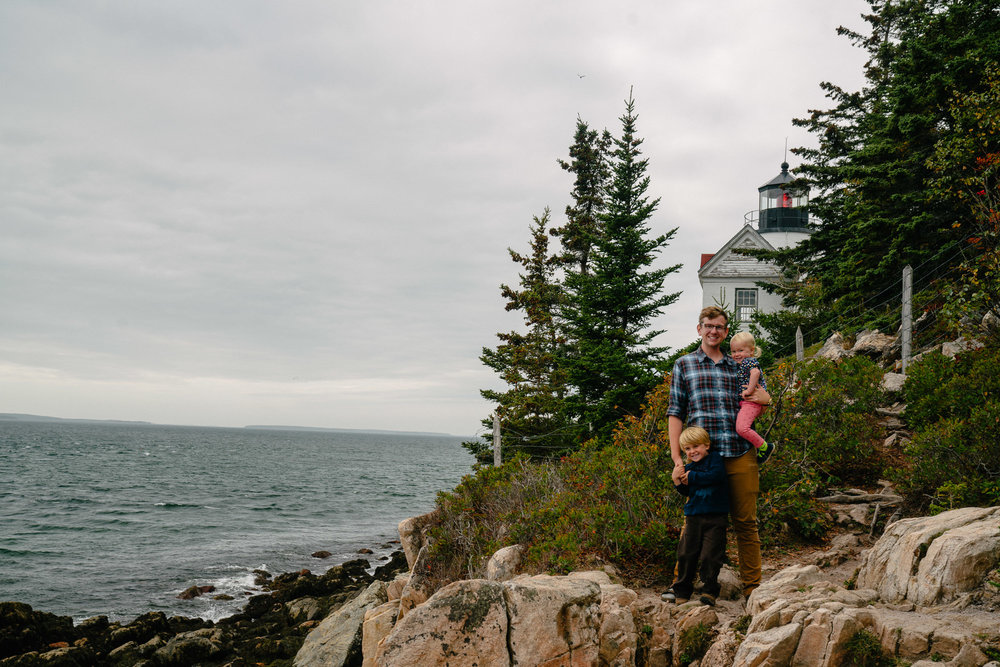 dad and kids with lighthouse on maine coast