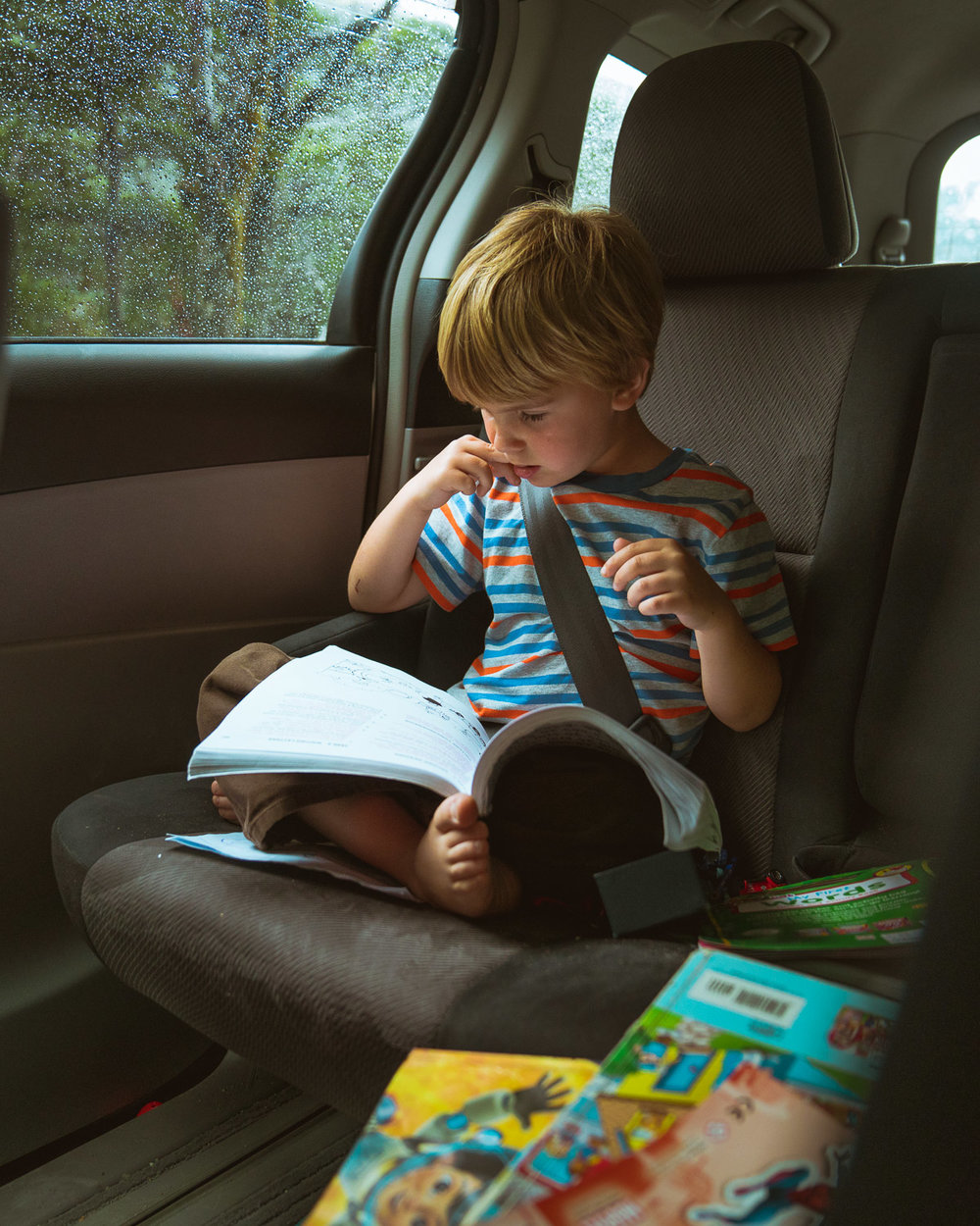 Sitting in his Mifold car seat, surrounded by the books that kept him occupied for 2 months of travel!