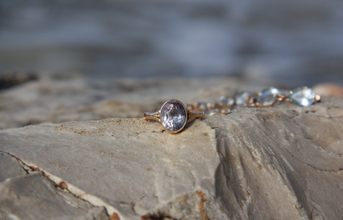 Alexandrite ring sitting on a rock by the sea