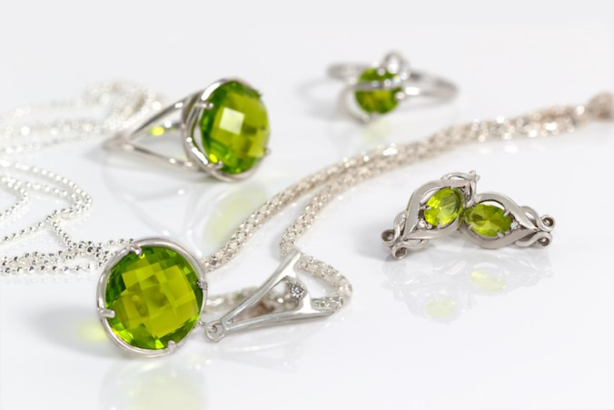 Peridot jewelry, include silver earrings, a necklace on silver chain, and two rings displayed on white acrylic desk