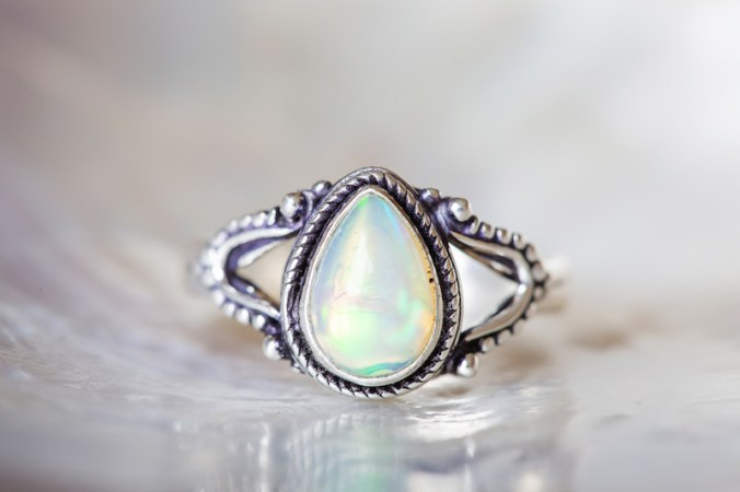 Silver ring with opal mineral gemstone on pearl background