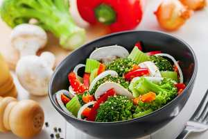 Steamed broccoli, mushrooms, and peppers in a bowl
