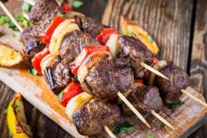 Five grilled beef shishkabab skewers on a cutting board