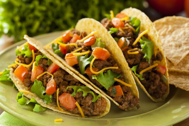 Three ground beef hardshell tacos with cheese, lettuce, tomatoes