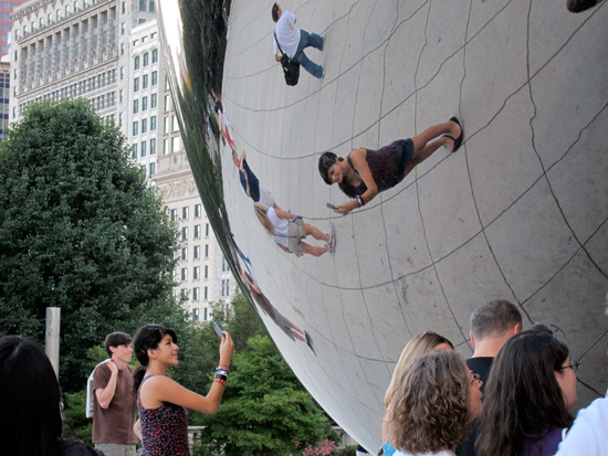 """Young woman photographing her reflection in """"the Bean"""" (Credit: Susan Barsy)"""