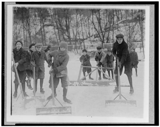 Boys with ice-shovels pose for their pictures while clearing snow off a pond.