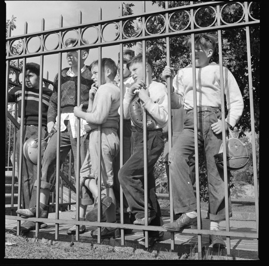 Boys watching a football game hanging on a fence.