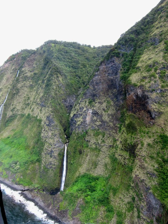 aerial view of coastal cliffs and waterfall.