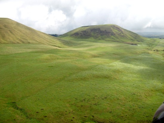 The undulating green surface of north Hawaii Islands drapes over the forms of dormant volcanic peaks.