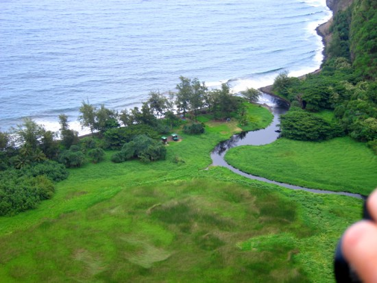 Low aerial view of two campers near the edge of a sea valley along the North Kohala coast.