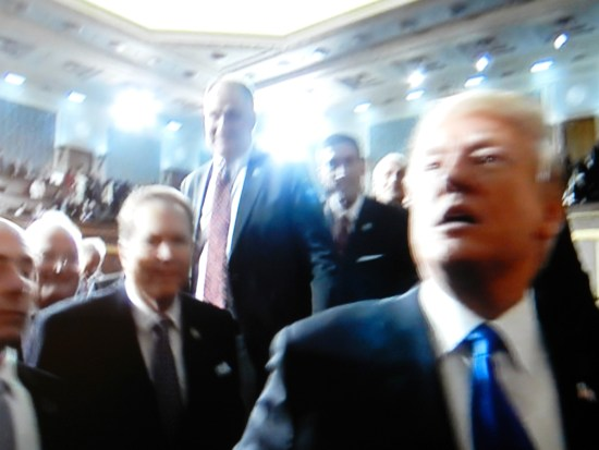 Low-angle shot of Trump and smiling lawmakers.