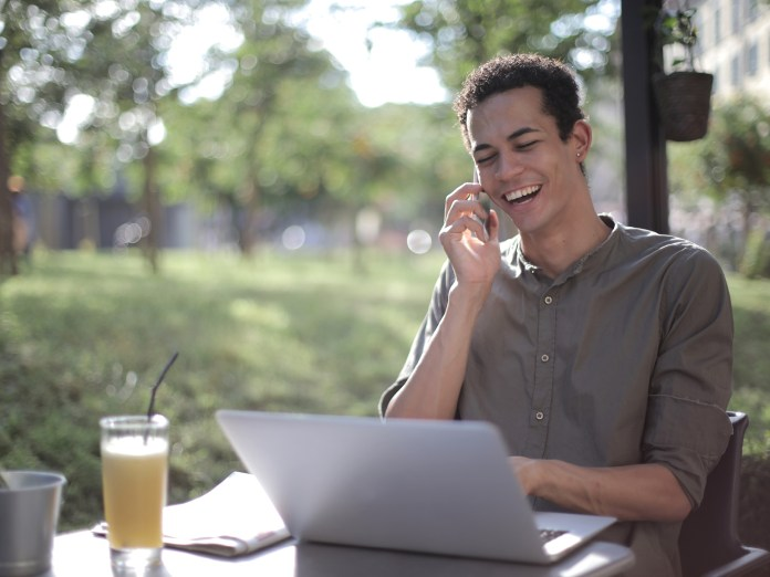 man on the phone looking at laptop