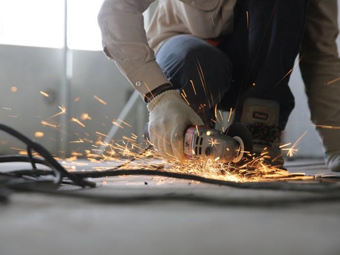 man sawing through metal