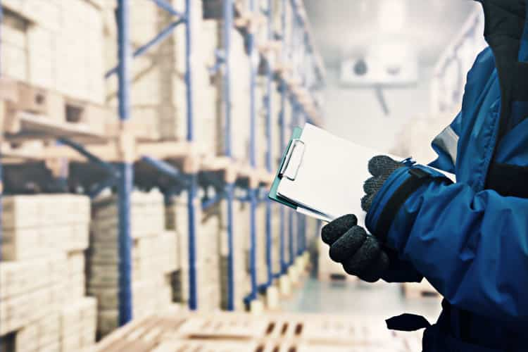 Worker inspecting inventory in a warehouse